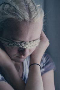 woman covering eyes using braided hair